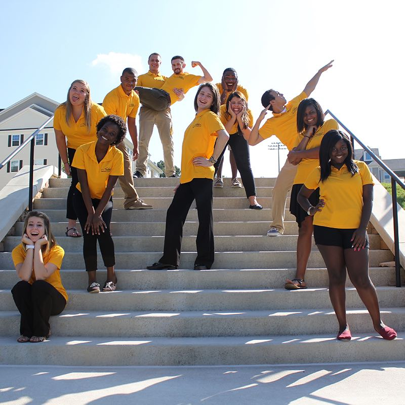 Residential Assistants RAs pose on some stairs.